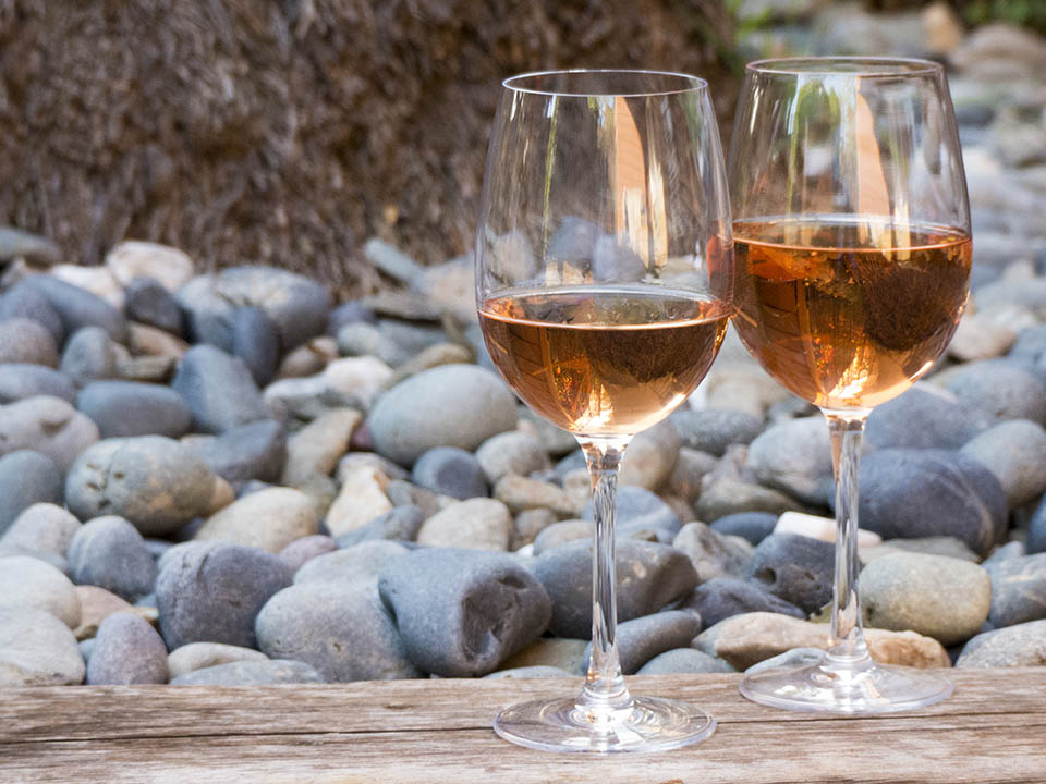 Two glasses of rose wine perched on wood ledge with a rock backgr